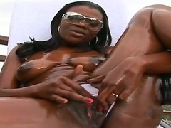 Crazy ebony slut shows her oiled body and masturbates with her fingers